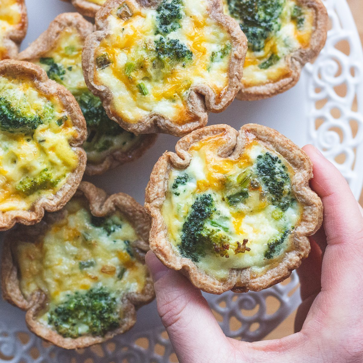 Hand holding small quiche with sprouted spelt crust