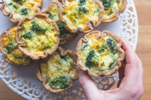 A person holding a sprouted spelt mini quiche